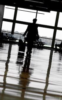 Homem andando com bagagem no terminal do aeroporto