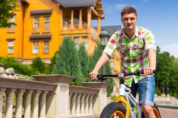 Homem andando de bicicleta amarela e colorida, passando por uma casa pintada de amarelo em uma estrada pavimentada com tijolos, vista de baixo ângulo