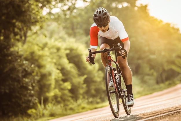 Homem andando de bicicleta ao pôr do sol a imagem do ciclista em movimento no fundo à noite