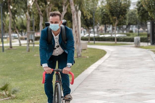 Homem andando de bicicleta com máscara médica