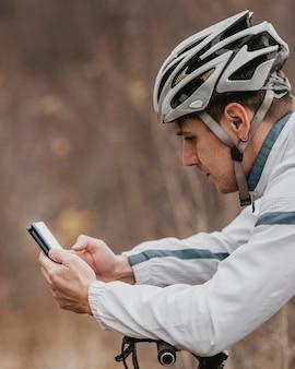 Homem andando de bicicleta de montanha e verificando o telefone