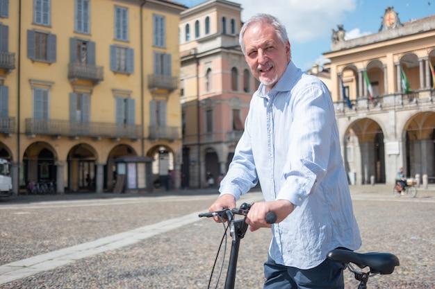 Homem andando de bicicleta em uma praça da cidade