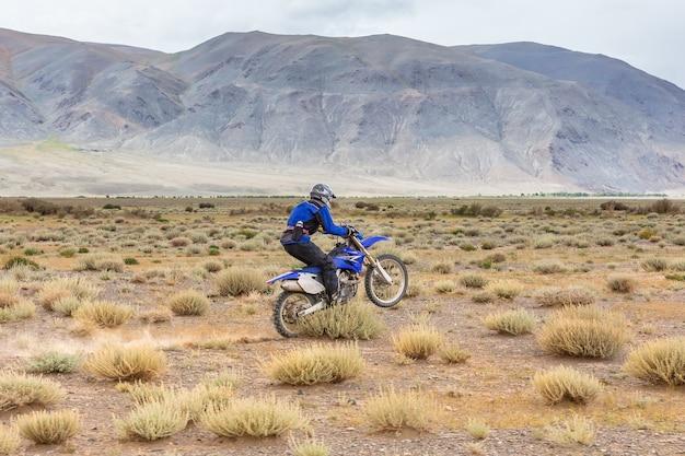 Homem andando de bicicleta motorizada nas estepes da mongólia, nas colinas da mongólia