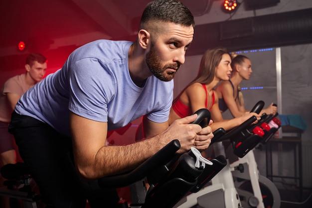 Homem andando de bicicleta na aula de spinning com amigos na academia, fazendo exercícios em bicicleta ergométrica, homem branco e forte está concentrado no treino
