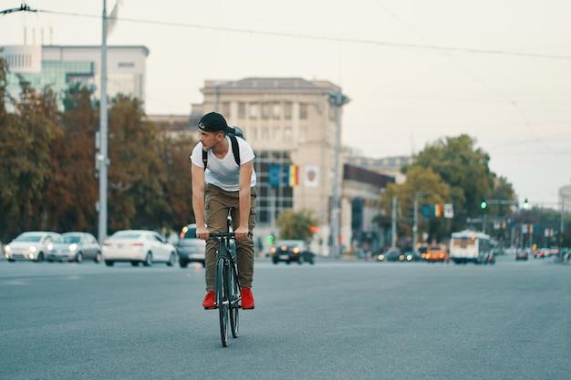 Homem andando de bicicleta na cidade urbana, de mãos dadas no guidão