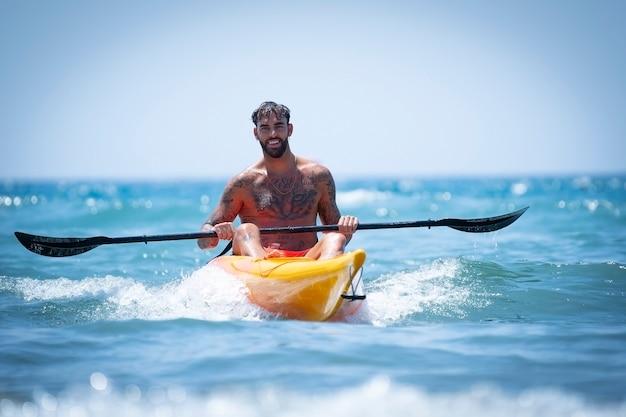 Homem andando de caiaque na praia durante as férias de verão