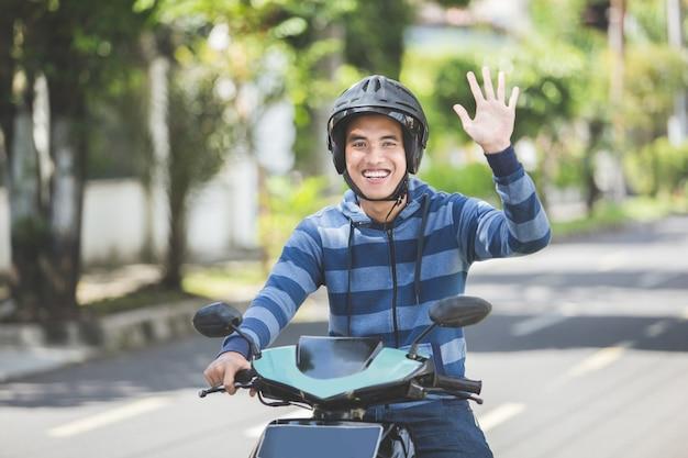 Homem andando de moto e acenando a mão