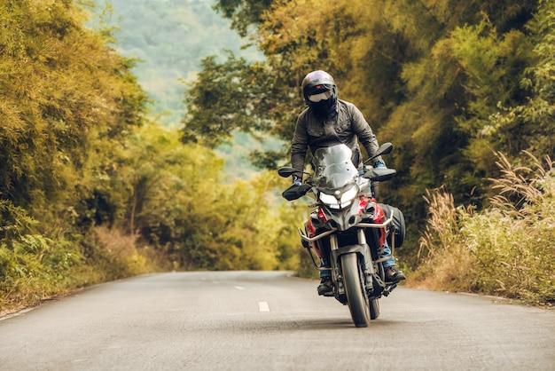 Homem andando de moto sportster na zona rural durante o pôr do sol