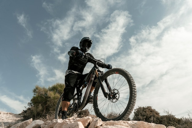 Homem andando de mountain bike de baixo ângulo