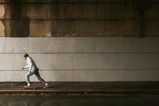 Homem andando de skate sob uma ponte com espaço de design de parede urbana