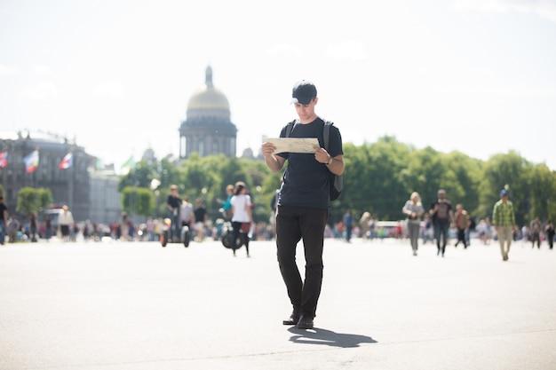 Homem andando e olhando um mapa