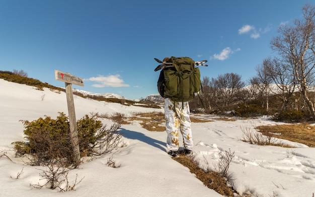 Homem andando em direção a reinheim, sinal mostrando o caminho para reinheim nas montanhas dovre na noruega