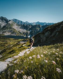 Homem andando em um caminho de pedra, rodeado por montanhas, plantas e um lago
