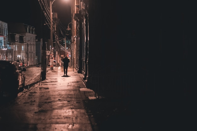 Homem andando na calçada durante a noite