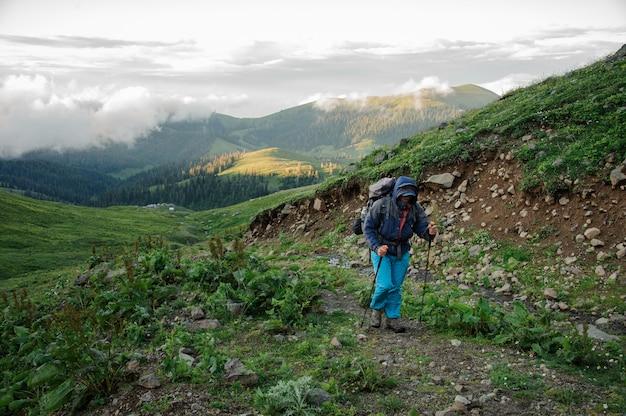 Homem andando na estrada de terra com caminhadas mochila e paus na colina