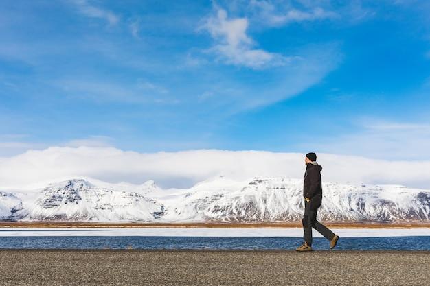 Homem andando na estrada, neve e montanhas