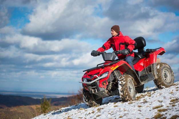 Homem andando na moto quad vermelho de quatro rodas