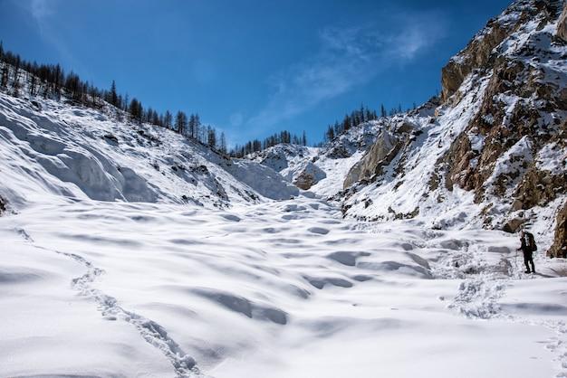Homem andando na neve com o fundo da montanha de neve.