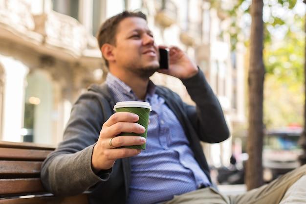 Homem andando na rua tomando café falando ao telefone