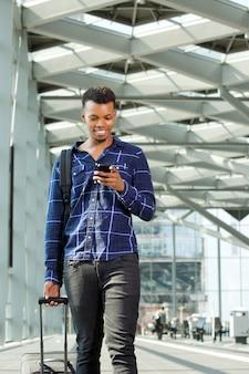 Homem andando no aeroporto com bagagem e telefone inteligente
