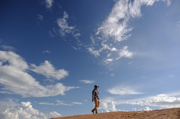 Homem andando no chão. homens asiáticos usam camisas cinzas, calças marrons estão de pé ao ar livre. olhe para o espaço da cópia. use um chapéu e lenço. homem de pé no chão em um dia nublado e com sol.