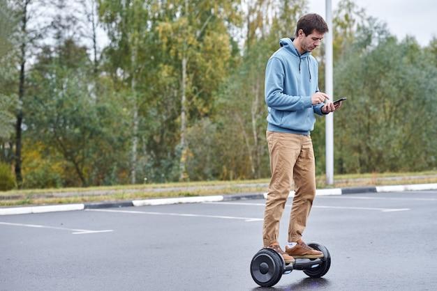 Homem andando no hoverboard e usando o smartphone ao ar livre