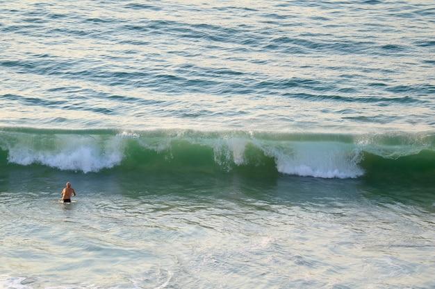 Homem, andar, em, um, grande, ondas, de, oceano atlântico, em, copacabana, praia, em, rio de janeiro, brasil
