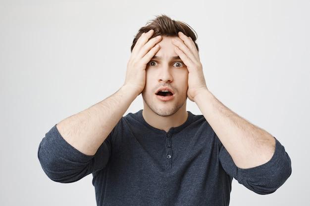 Homem angustiado e assustado agarrando a cabeça e ofegando em choque