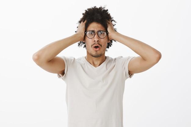 Homem angustiado e perturbado agarra a cabeça e parece alarmado, em pânico, tendo problemas