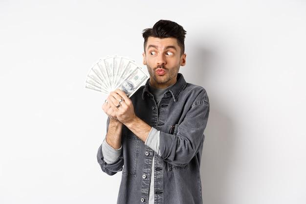 Homem animado, abraçando e beijando as notas de dólar, segurando dinheiro e regozijando-se, de pé sobre um fundo branco.