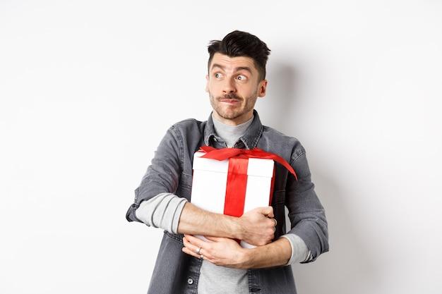 Homem animado, abraçando um presente romântico para a namorada, esperando o dia dos namorados com o amante, olhando para o logotipo do espaço vazio com uma cara feliz, de pé no fundo branco.