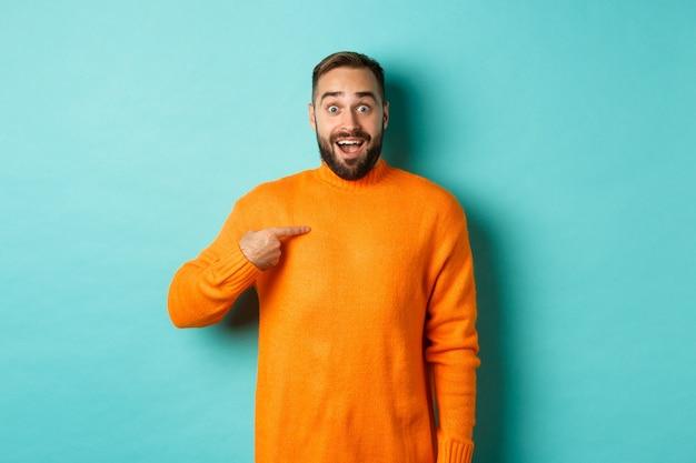Homem animado, apontando para si mesmo, parecendo surpreso e feliz, sendo escolhido, em pé sobre um fundo azul claro.