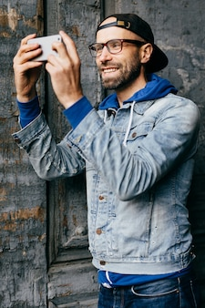 Homem animado com barba e bigode, vestindo camisa jeans na moda com gancho e jeans, olhando alegremente