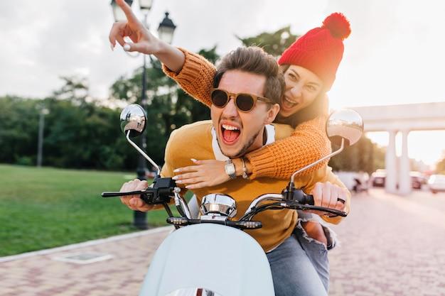 Homem animado com óculos escuros da moda curtindo um passeio rápido com uma linda amiga