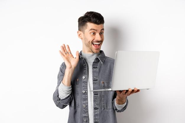 Homem animado, dispensando a mão no laptop, conversando por vídeo no computador e sorrindo amigável, de pé sobre fundo branco.