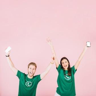 Homem animado e mulher com smartphone, levantando os braços