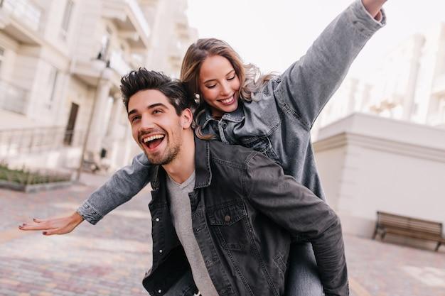 Homem animado em jaqueta jeans preta, relaxando com a namorada. retrato ao ar livre de casal feliz, explorando a cidade.