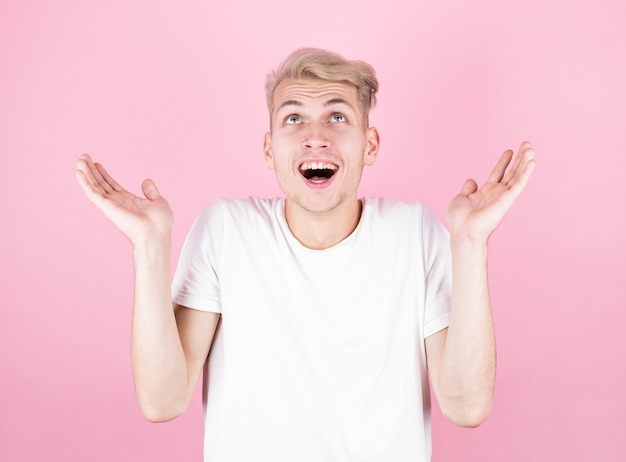 Homem animado espantado, mantém as mãos levantadas, encara a câmera, diz omg ou uau