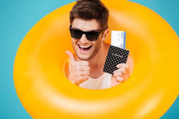 Homem animado feliz em óculos de sol, olhando através do anel inflável