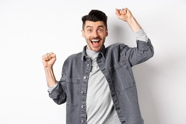 Homem animado gritando de alegria, ganhando prêmio e regozijando-se, levantando as mãos e gritando sim com cara de satisfeito, triunfando, atingir a meta, pisando em um fundo branco