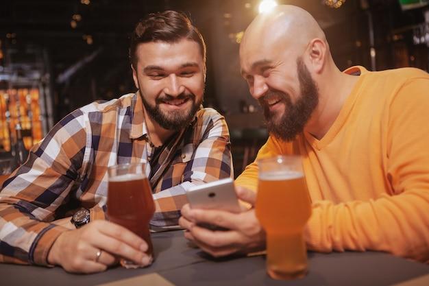 Homem animado mostrando algo on-line para seu amigo enquanto bebia juntos