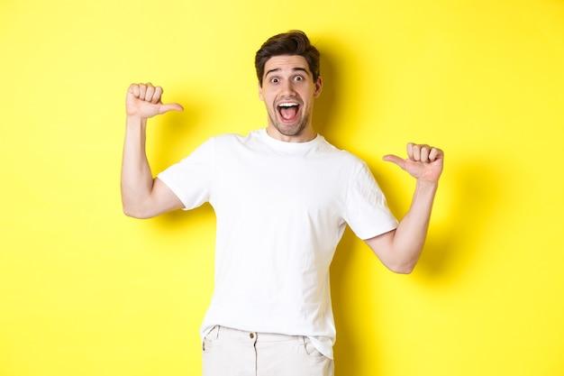 Homem animado, parecendo feliz, apontando para si mesmo com espanto, em pé sobre um fundo amarelo.