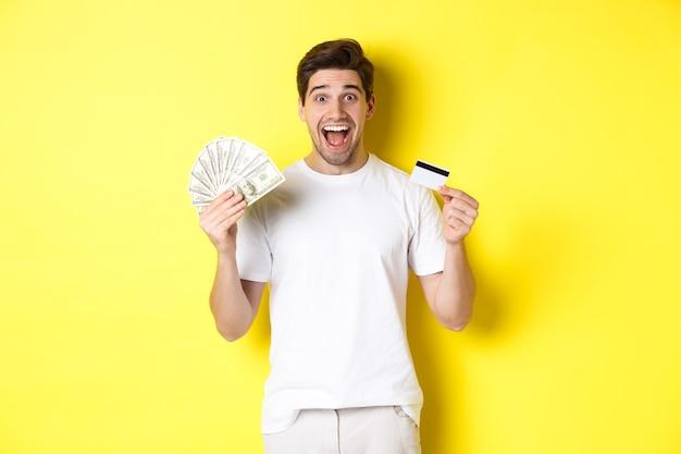 Homem animado, pronto para fazer compras de sexta-feira negra, segurando dinheiro e cartão de crédito, em pé sobre fundo amarelo.