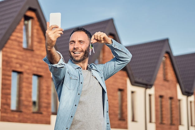 Homem animado tirando uma foto de si mesmo com as chaves