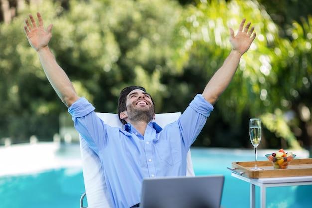 Homem animado usando um laptop perto da piscina
