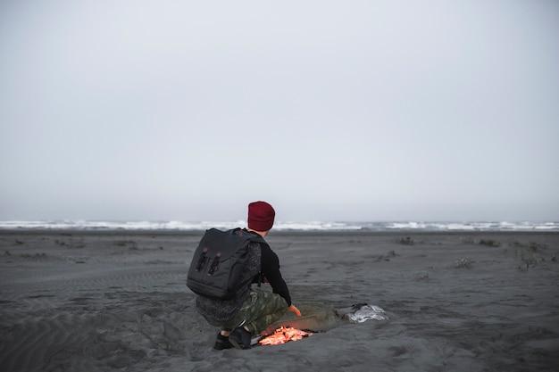 Homem anônimo aquecimento perto do fogo