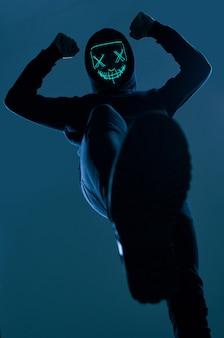Homem anônimo de capuz preto, escondendo o rosto atrás de uma máscara de néon