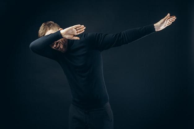 Homem anônimo em roupa elegante preta, cobrindo o rosto com as mãos dançando na parede preta