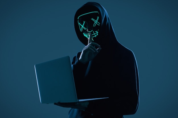 Homem anônimo em um capuz preto e máscara de néon invadindo um computador