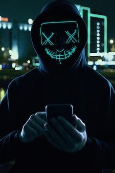 Homem anônimo em um capuz preto e máscara de néon invadindo um smartphone